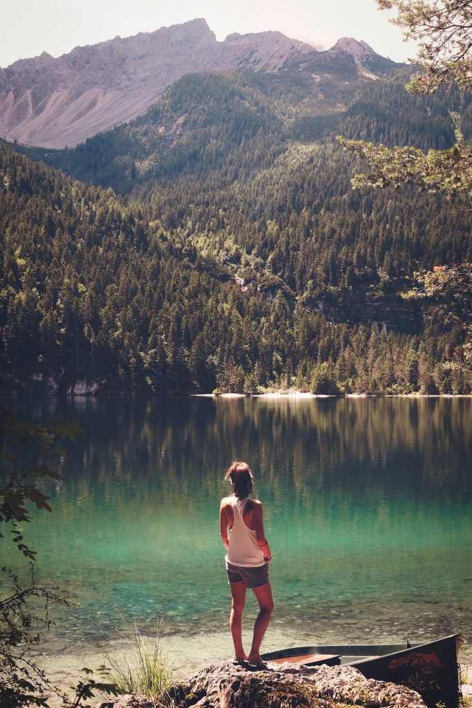 woman standing by mountain lake